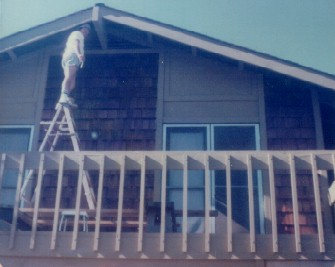 1970s - dad up a ladder on balcony above garage.